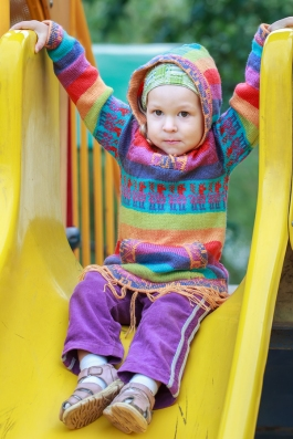 Toddler girl wearing woolen knitted sweater with hood is sitting